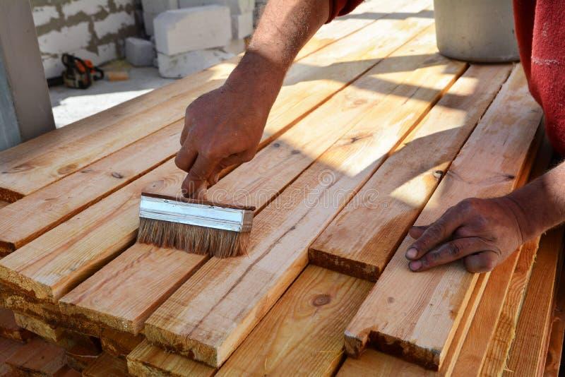 El trabajador de construcción está trabajando con el haz de madera El trabajador cepilla el líquido preservativo en los tableros  foto de archivo libre de regalías