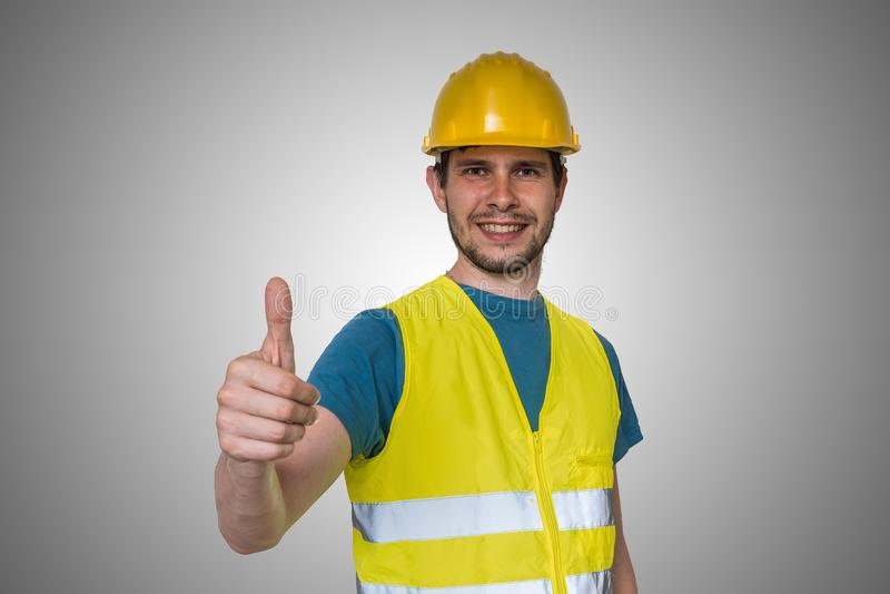 El trabajador de construcción feliz joven en casco amarillo está mostrando los pulgares encima del gesto fotografía de archivo
