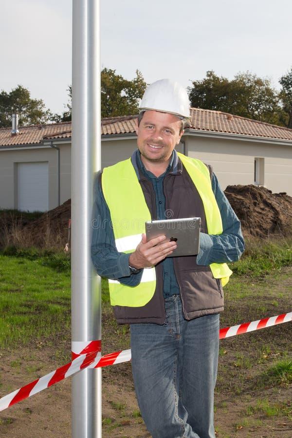 el trabajador de construcción hermoso del hombre es cojín lookking sonriente de la tableta fotos de archivo