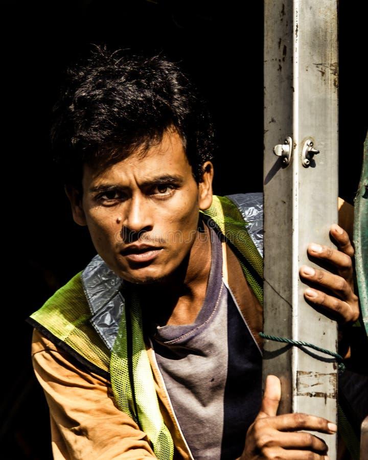 El trabajador de construcción indio mira en la cámara imagen de archivo