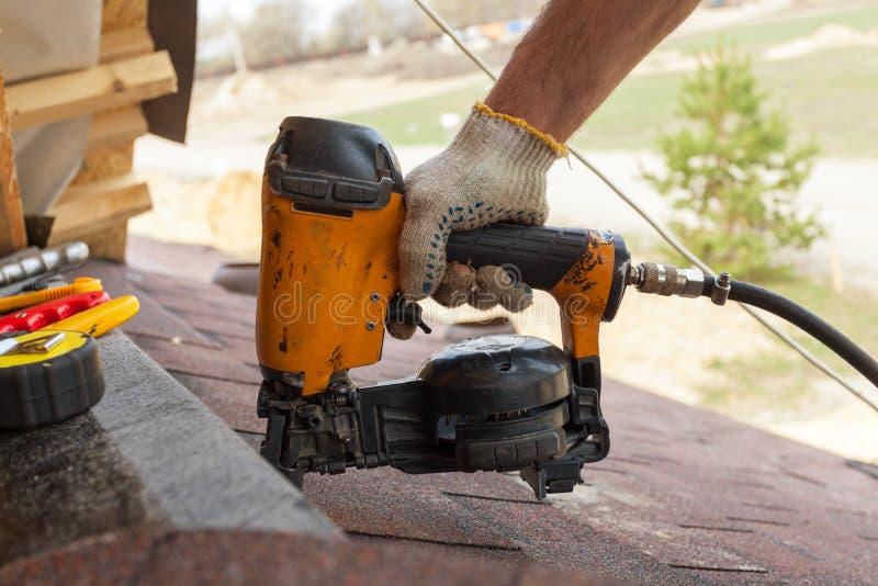 El trabajador de construcción que pone las tablas de la techumbre de asfalto con el clavo dispara contra en un desarrollo comerci fotografía de archivo libre de regalías