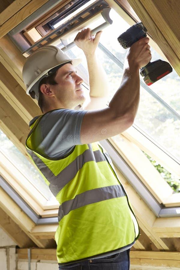 El trabajador de construcción Using Drill To instala la ventana fotos de archivo libres de regalías