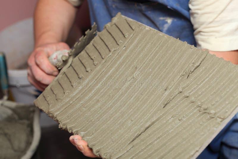 El trabajador de construcci?n est? tejando el pegamento del suelo de baldosas foto de archivo libre de regalías