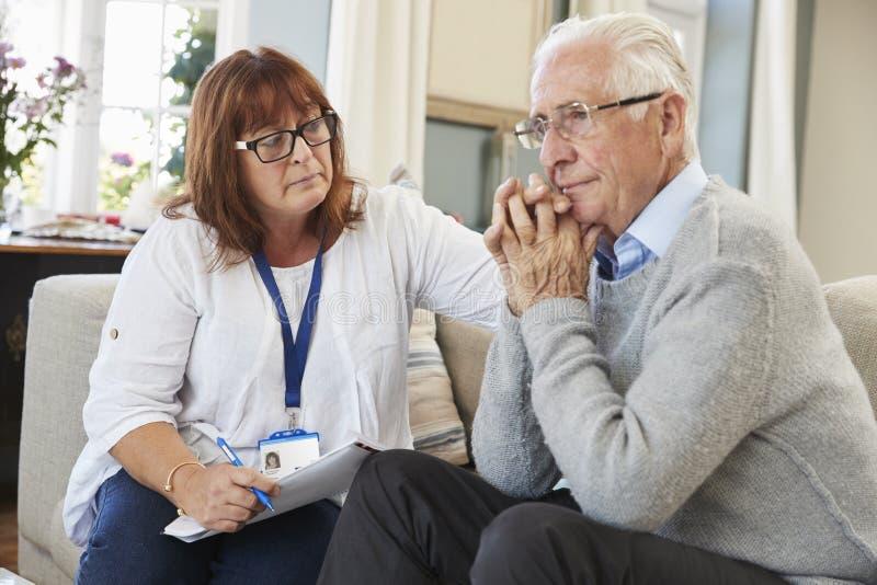 El trabajador de la ayuda visita al hombre mayor que sufre con la depresión foto de archivo