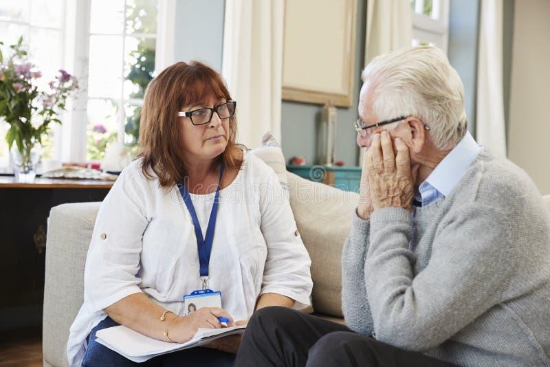 El trabajador de la ayuda visita al hombre mayor que sufre con la depresión imágenes de archivo libres de regalías