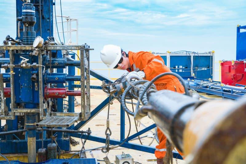 El trabajador de la plataforma petrolera examina y poniendo las herramientas del lado superior para la seguridad primero a la pro fotos de archivo libres de regalías
