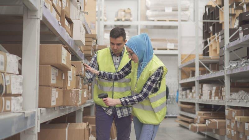 El trabajador de la tienda del hombre muestra a mujer musulmán cómo utilizar un escáner del código de barras imagen de archivo