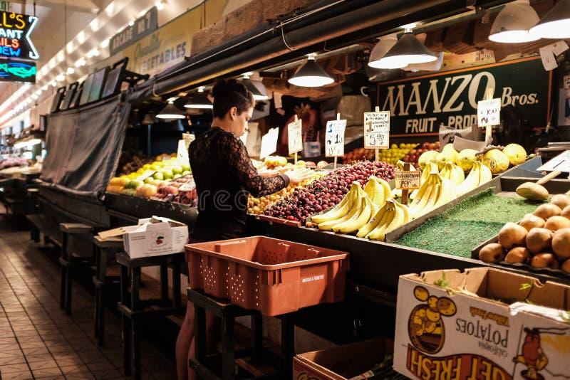 El trabajador de mujer arregla la fruta en el soporte de Manzo Brothers en el mercado de lugar de Pike imagen de archivo