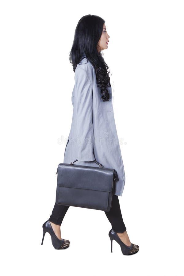 El trabajador de sexo femenino con la cartera camina en estudio fotografía de archivo libre de regalías