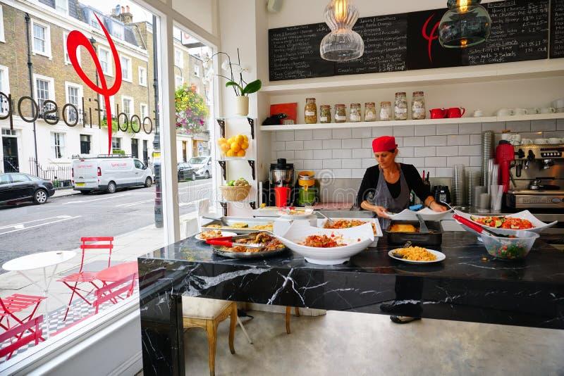 El trabajador de sexo femenino del restaurante prepara platos sanos en cocina del Street View fotos de archivo libres de regalías