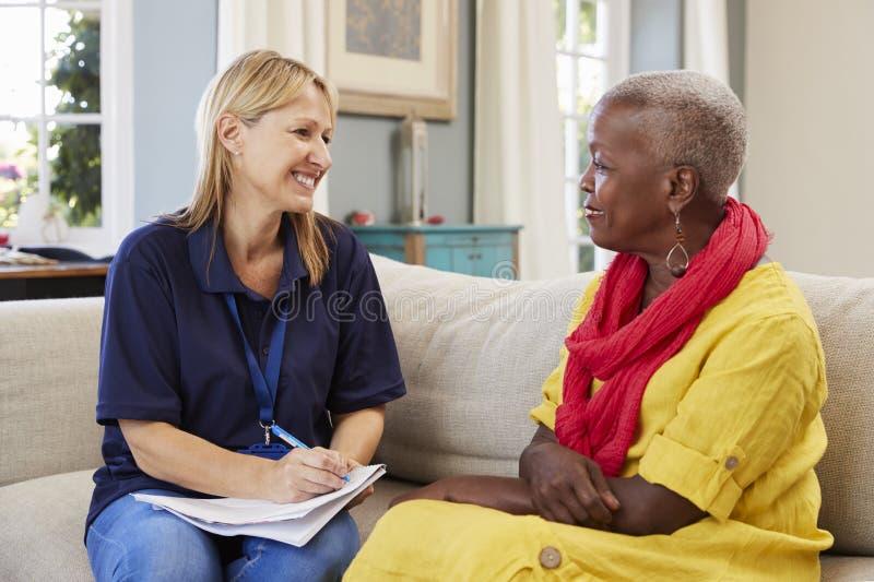 El trabajador de sexo femenino de la ayuda visita a la mujer mayor en casa fotografía de archivo libre de regalías