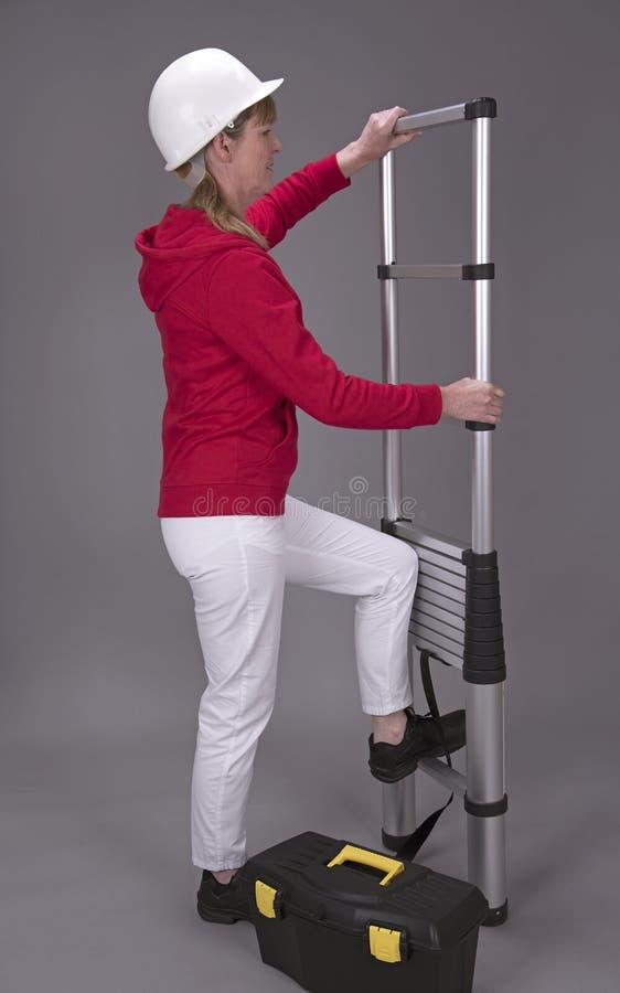 El trabajador de sexo femenino monta una escalera telescópica foto de archivo libre de regalías