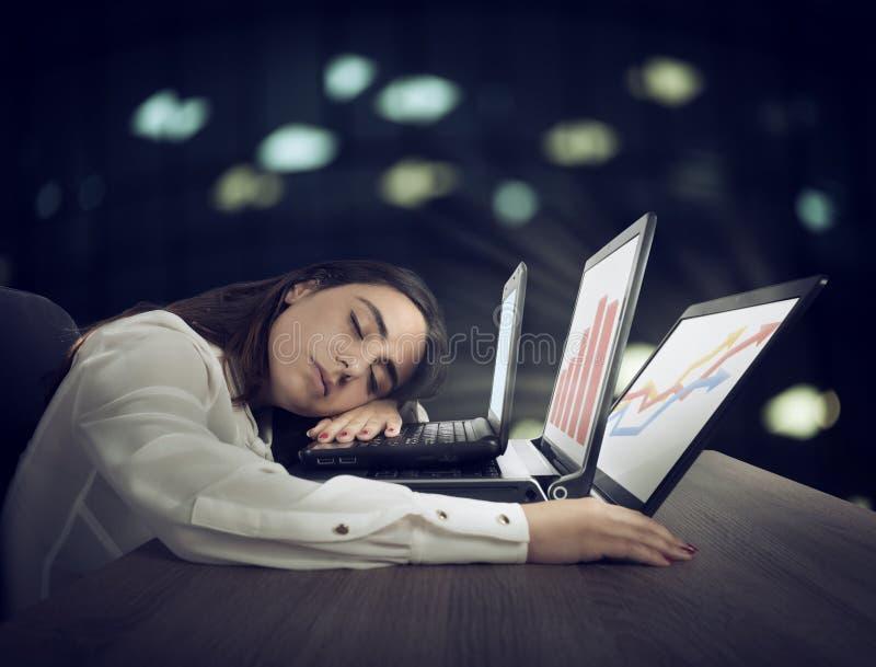 El trabajador de sexo femenino se cae dormido mientras que simultáneamente trabaja en tres ordenadores portátiles imágenes de archivo libres de regalías
