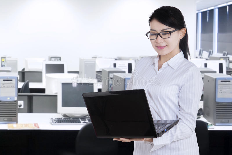 El trabajador de sexo femenino utiliza el ordenador portátil mientras que se coloca fotos de archivo