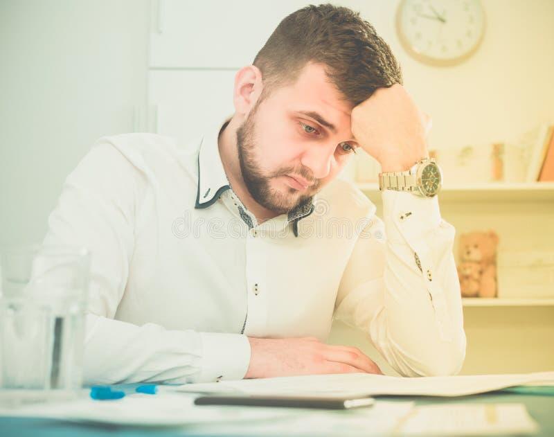 El trabajador de sexo masculino está teniendo problema complicado con proyecto imagenes de archivo