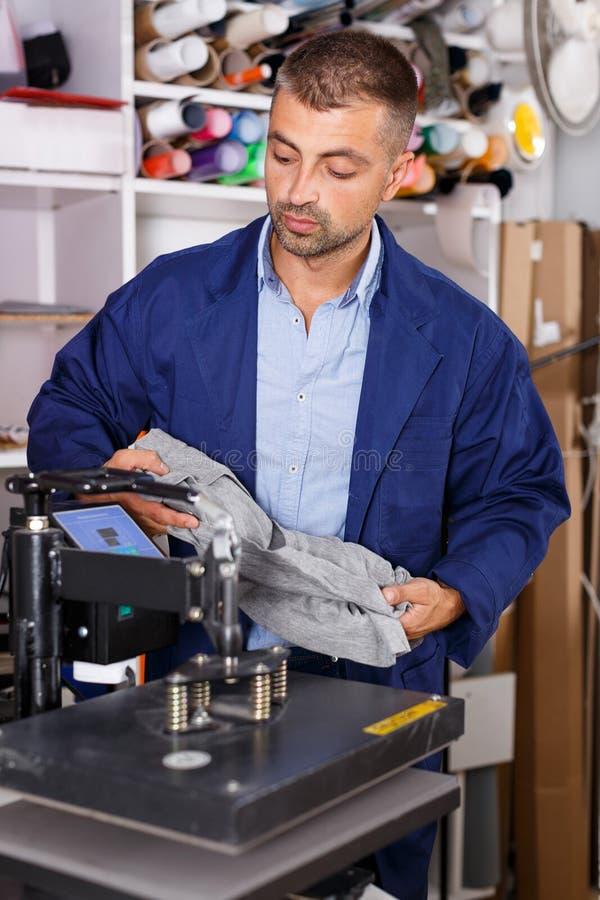 El trabajador de sexo masculino hace la impresión en la camisa imágenes de archivo libres de regalías