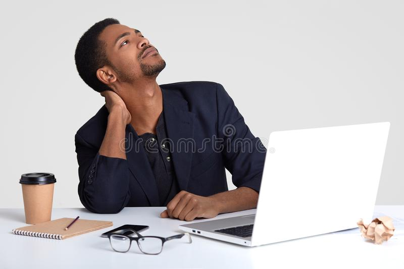 El trabajador de sexo masculino pelado oscuro soñador tiene dolor en cuello, guarda mirada hacia arriba, los trabajos por tiempo  imagen de archivo libre de regalías