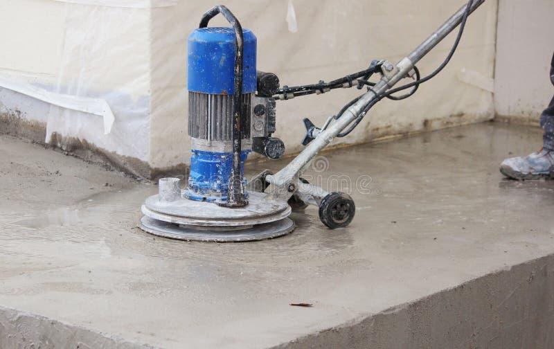 el trabajador de sexo masculino trabaja con la máquina de pulir del diamante, puliendo el pórtico delante del edificio de oficina fotos de archivo