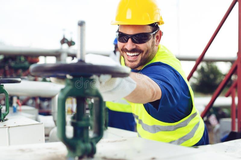 El trabajador del aceite cierra la válvula en el oleoducto foto de archivo