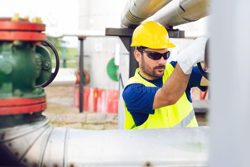 El trabajador del aceite cierra la válvula en el oleoducto fotos de archivo