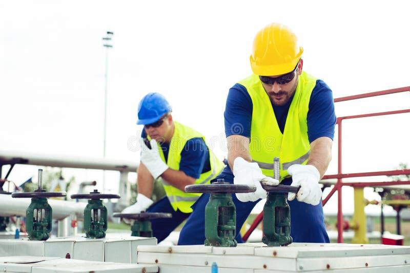 El trabajador del aceite cierra la válvula en el oleoducto imagen de archivo libre de regalías