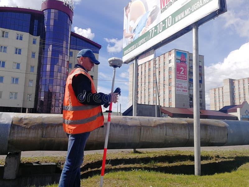 El trabajador del camino con un nivel escribe los indicadores en el diario fotografía de archivo