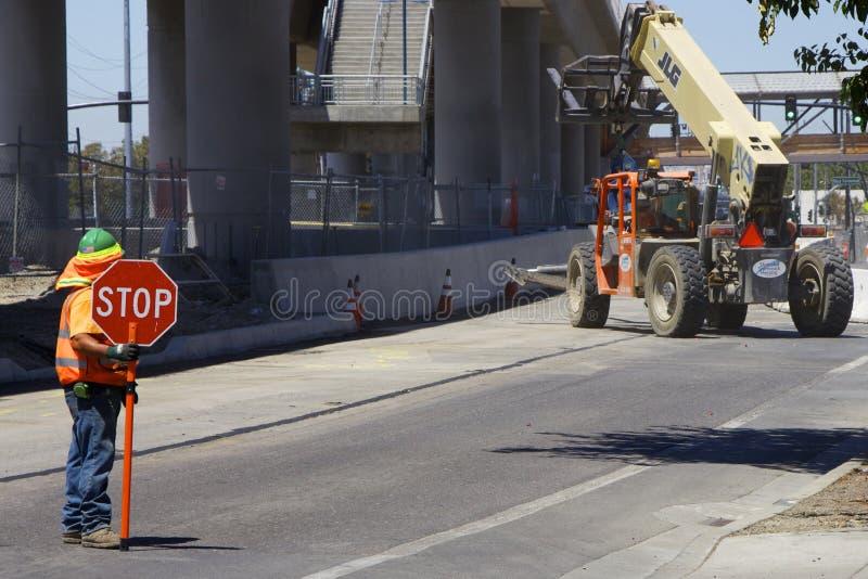 El trabajador del camino en un chaleco anaranjado muestra una parada de la señal de tráfico imagenes de archivo