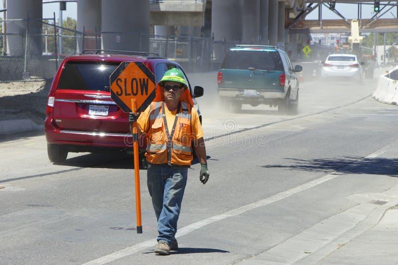 El trabajador del camino en un chaleco anaranjado muestra una señal de tráfico lenta fotografía de archivo