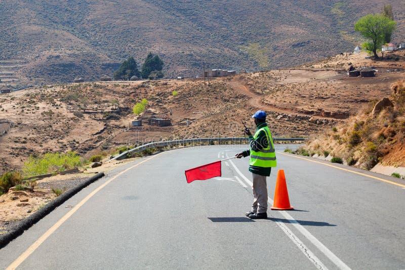 El trabajador del camino sostiene a disposición la bandera roja que prohíbe el tráfico, restricciones de viaje, reparación del ca fotos de archivo