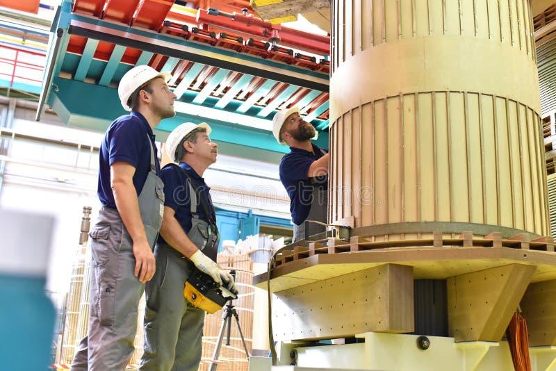 El trabajador del grupo monta un transformador en la ingeniería industrial - imagen de archivo libre de regalías