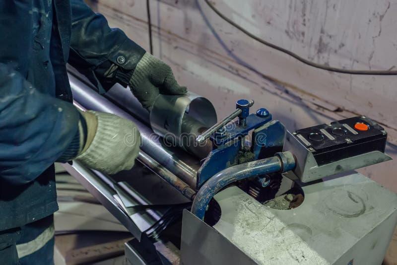 El trabajador del mecánico está haciendo las piezas de conexión para los tubos y los tubos del metal fotos de archivo
