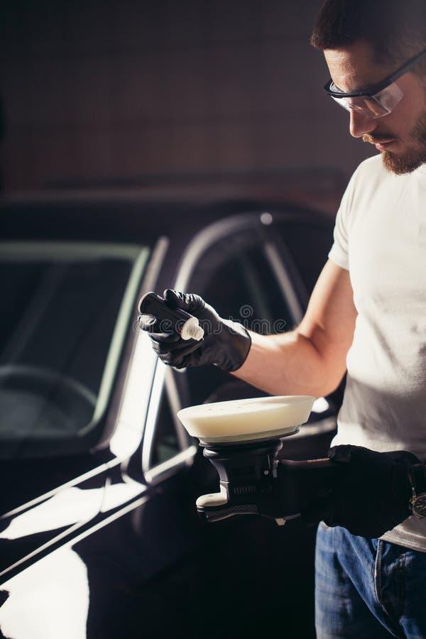 El trabajador del mecánico se prepara para el coche de pulido por la máquina del almacenador intermediario del poder imágenes de archivo libres de regalías