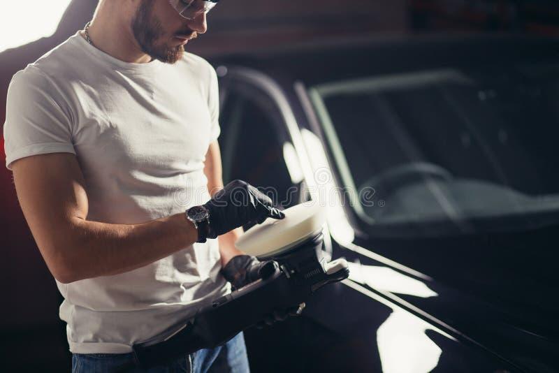 El trabajador del mecánico se prepara para el coche de pulido por la máquina del almacenador intermediario del poder foto de archivo