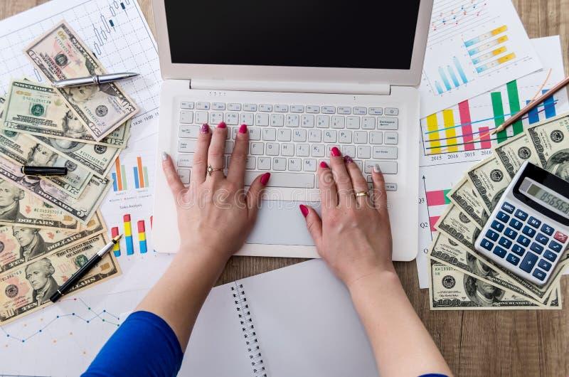 El trabajador del negocio está llevando a cabo dólares de EE. UU. disponibles con el ordenador portátil imagenes de archivo
