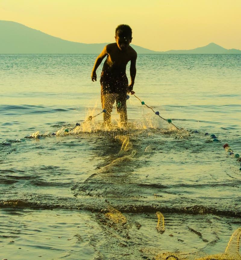 El trabajador del niño, con la red de pesca tirando en los días coge, foto de archivo