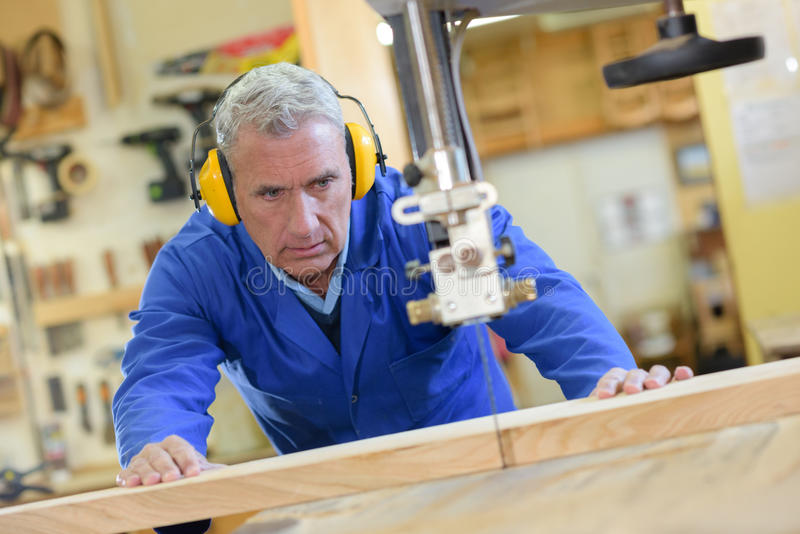 El trabajador dos en taller de los carpinteros usando vio la máquina fotografía de archivo libre de regalías