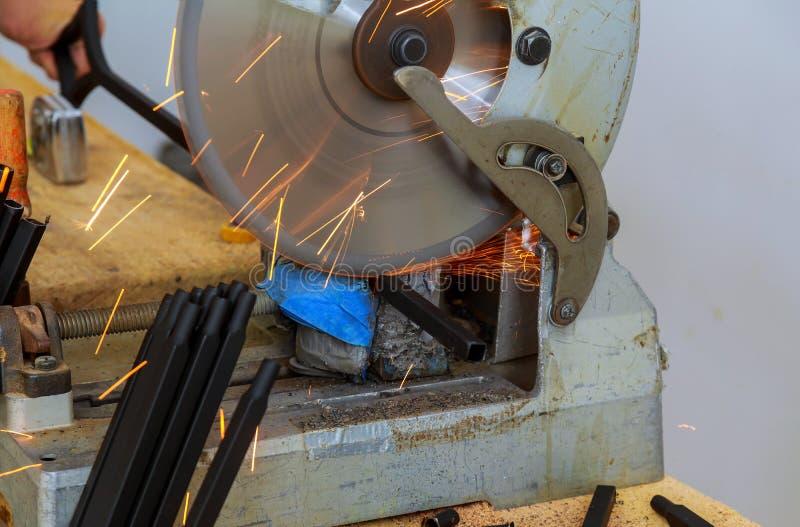 El trabajador en cortar un carril de acero con el electro circular vio imágenes de archivo libres de regalías