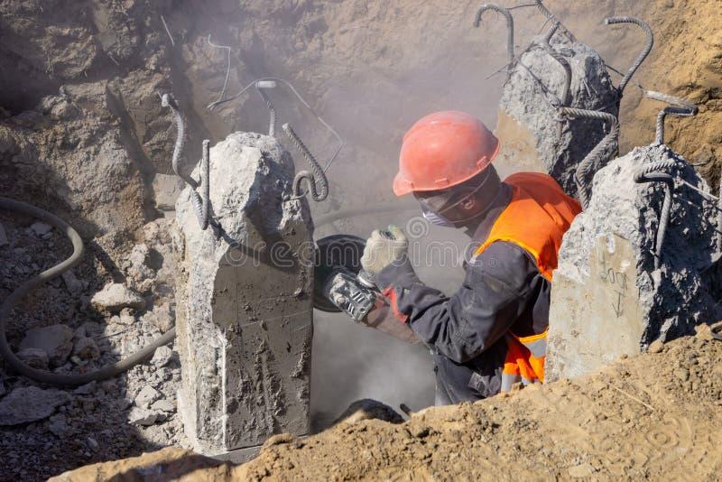 El trabajador en el emplazamiento de la obra corta el hormigón imagen de archivo