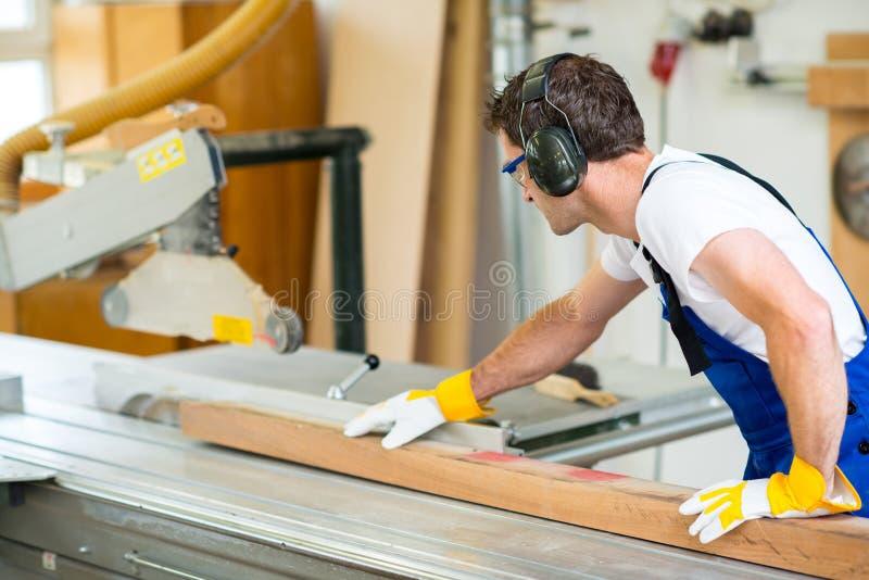 el trabajador en taller usando vio la máquina foto de archivo