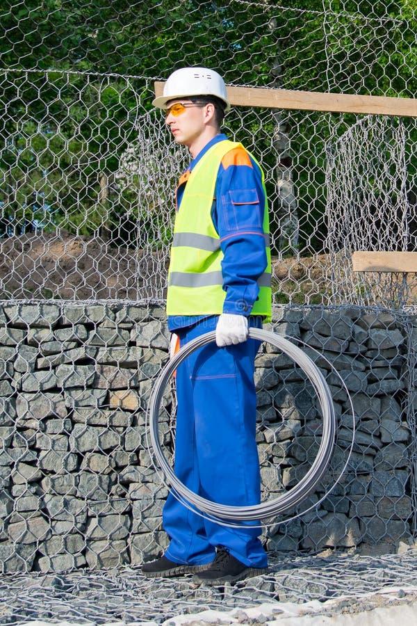 El trabajador en un chaleco amarillo y un casco blanco, lleva un rollo del alambre en su mano imagen de archivo