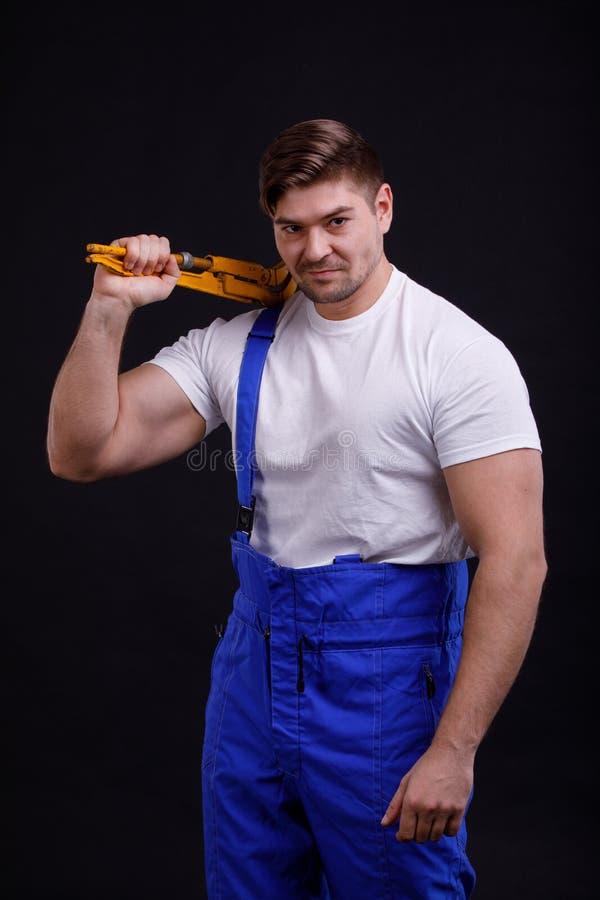 El trabajador en uniforme sostiene una llave ajustable en su hombro en un fondo negro fotografía de archivo