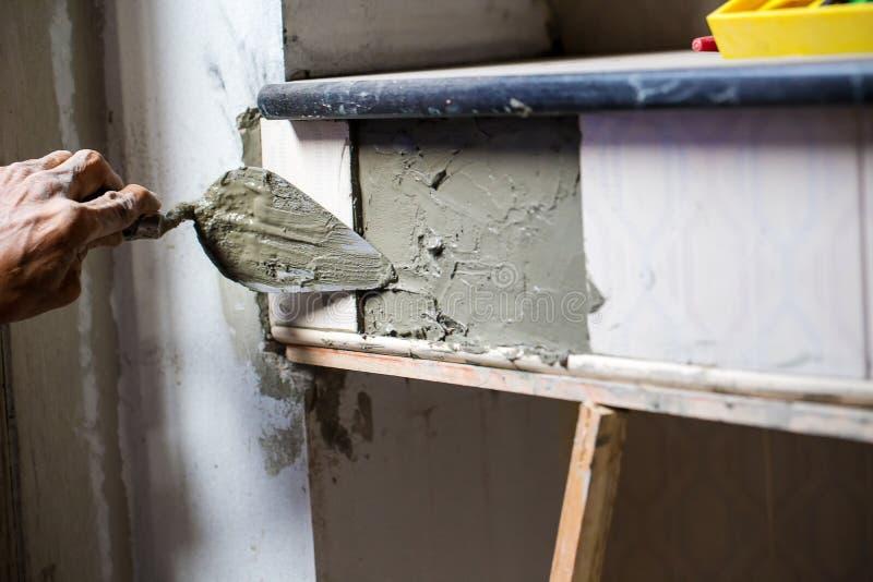 El trabajador está enyesando el cemento en la pared imagen de archivo