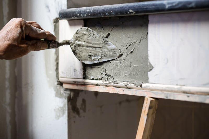 El trabajador está enyesando el cemento en la pared fotos de archivo