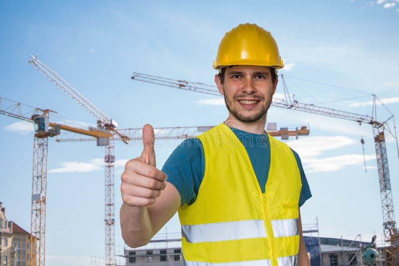 El trabajador feliz en emplazamiento de la obra está mostrando los pulgares encima del gesto imagen de archivo