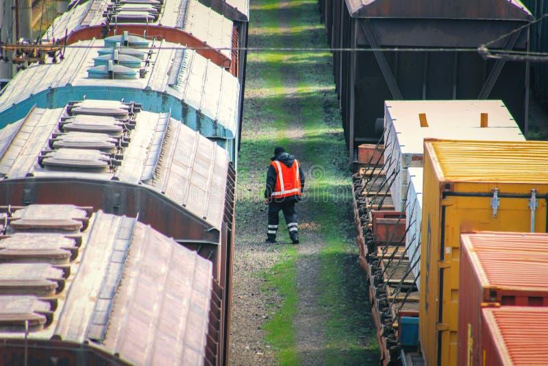 El trabajador ferroviario en guardapolvos con un martillo examina el coche de carga viejo foto de archivo