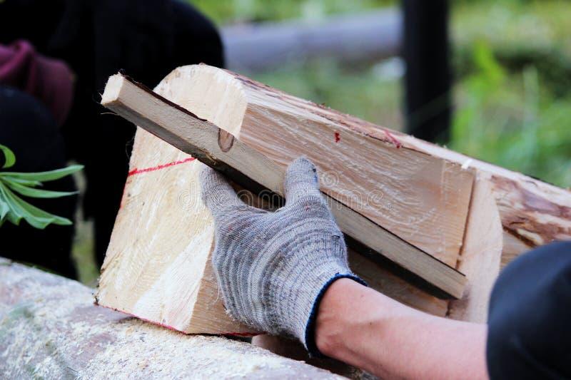 El trabajador hace una marca en el registro antes del edificio del blocao y utiliza el pasador de madera como margen de beneficio fotografía de archivo