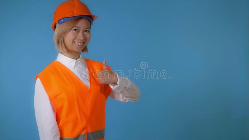 El trabajador hermoso en uniforme muestra la muestra como fotografía de archivo libre de regalías