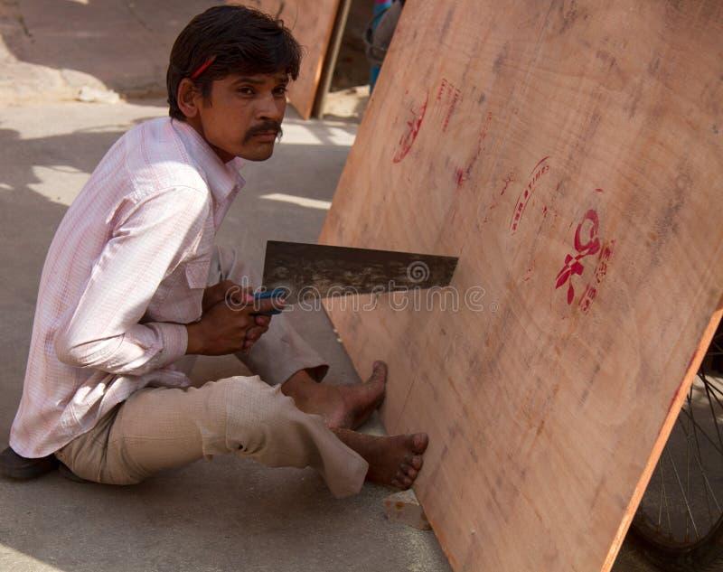 El trabajador indio asierra una hoja de la madera contrachapada imagen de archivo