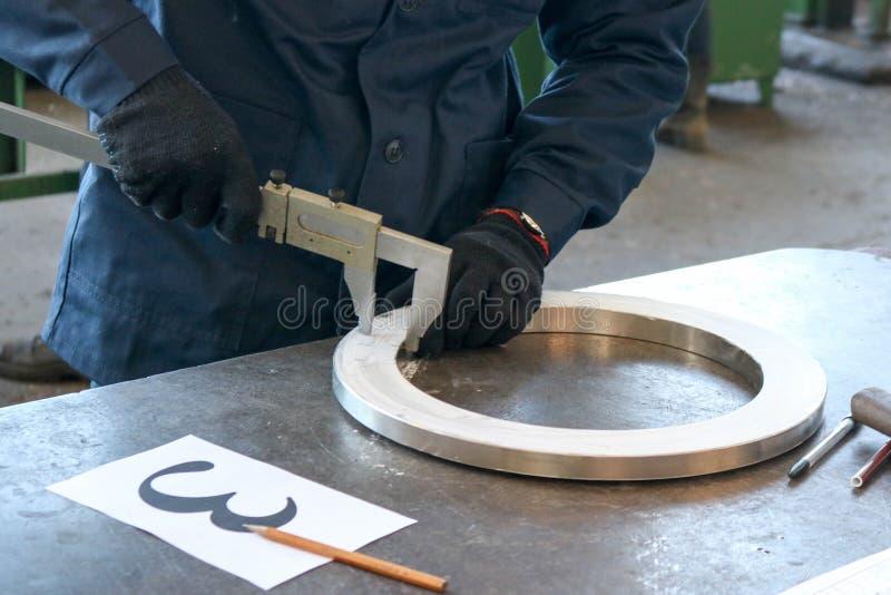 El trabajador, el ingeniero mide la pieza, el anillo brillante del metal, el reborde con un calibrador en la tabla de trabajo del fotografía de archivo