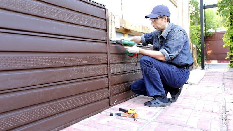El trabajador instala el apartadero plástico en la fachada fotografía de archivo